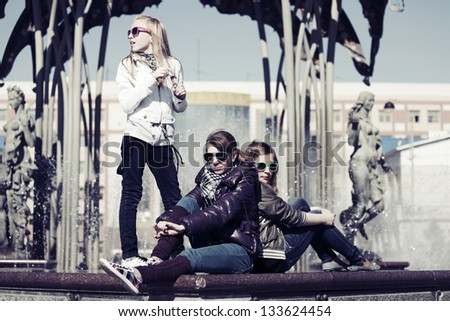 Group of teenage girls against a city fountain