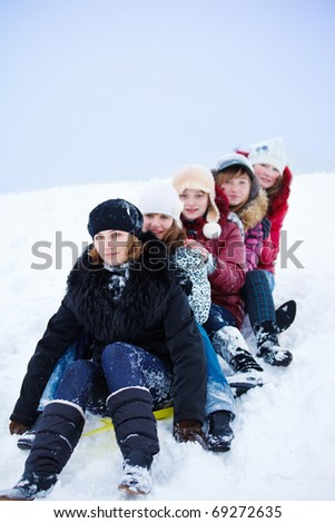 Group of teenage girls sledging from the hill