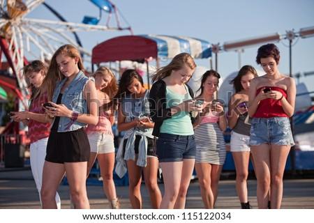 Group of 8 teenage girls text messaging at an amusement park - stock photo