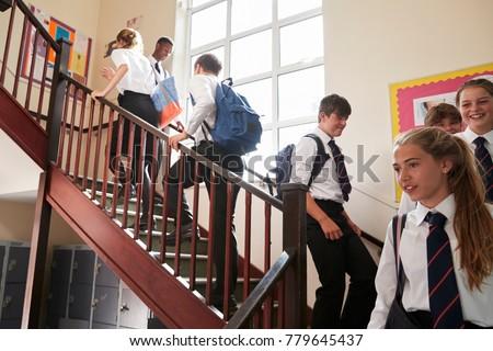 Group Of Teenage Students In Uniform Walking Between Classrooms