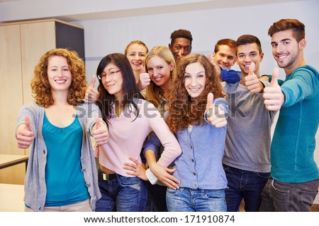 Group of teenager in a school classroom holding their thumbs up