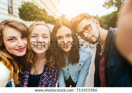Group of teenager students doing selfie over the university building huggins, smiling, back to school concept. Sun glare effect. Four young happy student making selfie and smiling outdoors. #711455986