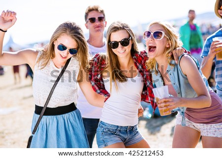 Group of teenagers at summer music festival, sunny day. Young teens at summer music festival. Funny group of young girls at music festival. Crazy teens with beer at summer festival.