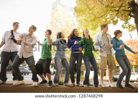 Group of teenagers dancing and having fun on top of a stone wall in the street.