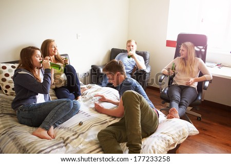 Group Of Teenagers Drinking Alcohol In Bedroom #177233258