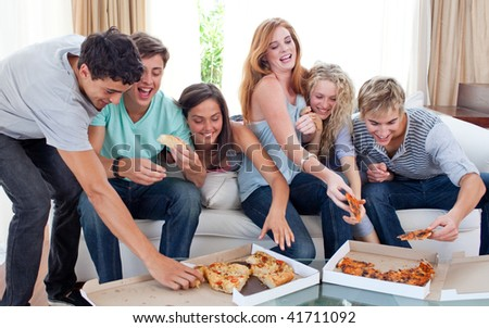 Group of teenagers eating pizza in the living-room on the sofa