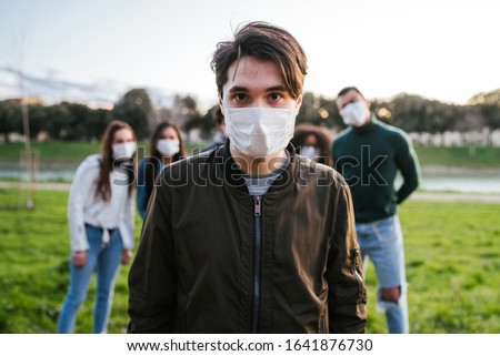 Group of teenagers friends at park wearing medical masks to protect from infections and diseases - Conceptual Coronavirus virus quarantine - Copy space - Multiracial people having fun together