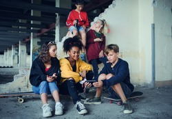 Group of teenagers gang sitting indoors in abandoned building, using smartphones.