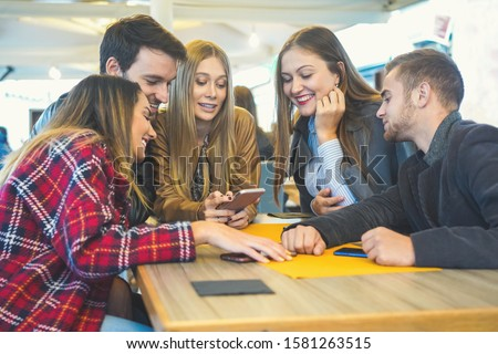 Group of teenagers hangging out in a bar and using smartphones - Girl showing her friends the new online stuff like photo, video - Obsessed in technology concept Stock fotó ©