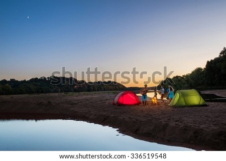 Group of teenagers having fun at sunset on the beach. They are camping with two red and green tents They are playing guitar and dancing around a camp fire. They are wearing summer hats and sunglasses