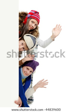 Group of teenagers in warm clothes looking out white board.