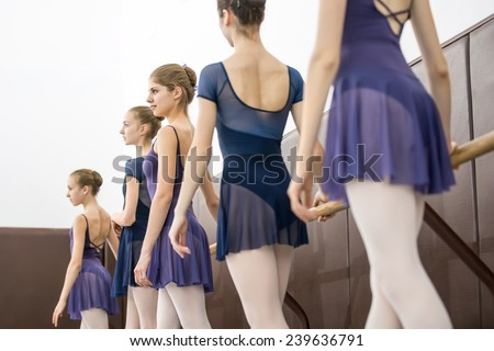 group of teenagers involved in choreographing the dance hall near the barre