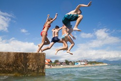 Group of teenagers jumping off the pier into the sea. fun summer vacation