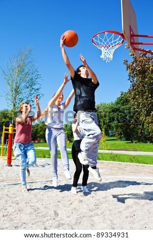 Group of teenagers playing street basketball