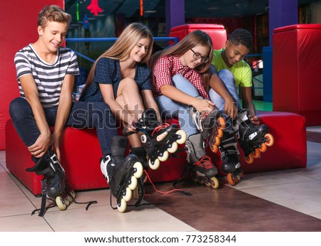 Group of teenagers putting on roller skates indoors