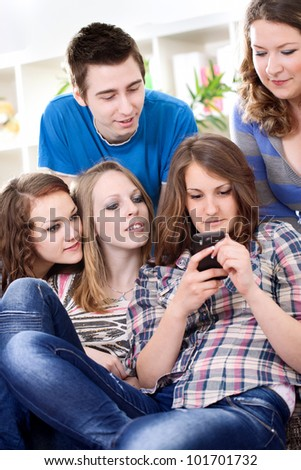 Group of teenagers reading interesting sms on smart phone