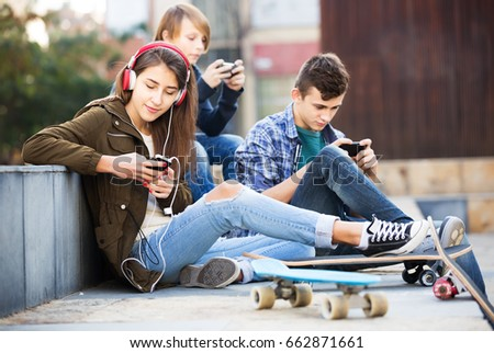 Group of teenagers relaxing with cell phones in the city #662871661