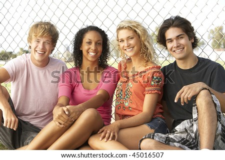 Group Of Teenagers Sitting In Playground