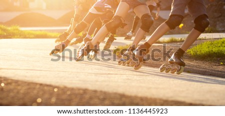 Group of teenagers skating on track in summer evening. Abstract panoramic short track speed skating sport background