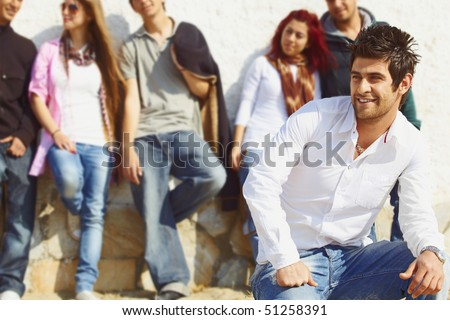 group of teenagers standing against the wall with their leader in white shirt and jeans sitting infront