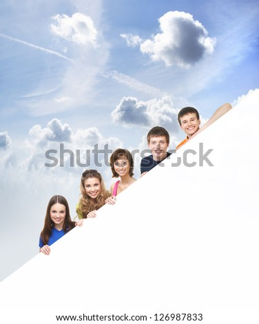 Group of teenagers with a giant, blank, white billboard over the sky background