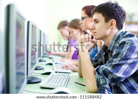 group of teens in internet-cafe with computers