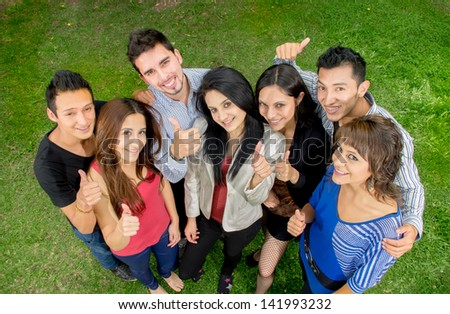 Group of teens thumbing up outdoors