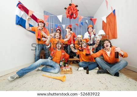 Group of ten cheering sports fans watching their national sports team at home