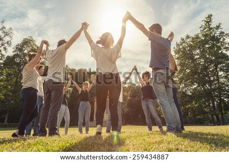 Group of ten friends at the park holding hands