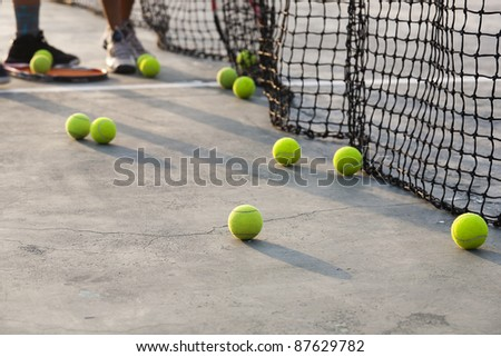 group of tennis balls, boy collecting tennis balls from the court after practice session.
