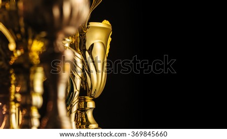 Group Of The Golden Trophies In Sparkling Light On Dark Background 369845660