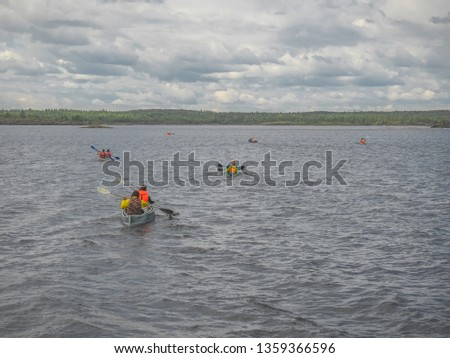 Group of the kayaks with rowers in life vests with paddles moves through the Ladoga lake, Karelia, Russia. Boats with oarsmans on water surface and stony shores with forest on horizon. Cloudy weather