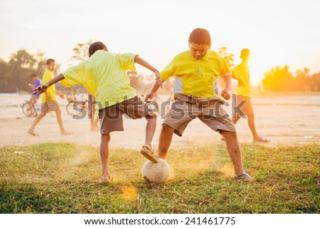 Group of the kids (boys) are playing soccer football for exercise in the sunshine day. - Shutterstock ID 241461775