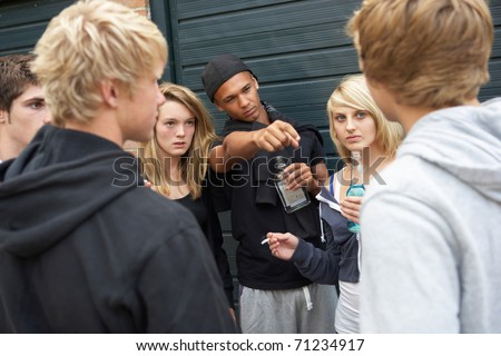 Group Of Threatening Teenagers Hanging Out Together Outside Drinking