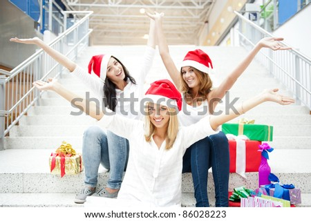 Group of three beautiful girls sitting on stairs at shopping mall hall wearing santa clause red hats with open arms