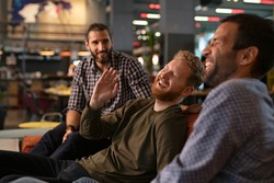 Group of three best friends laughing and enjoying the evening at pub. Happy young men enjoying late night staying together at bar. Cheerful guys sitting on couch and having fun while relaxing.
