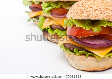 group of three big tasty  cheeseburgers in a row on white background