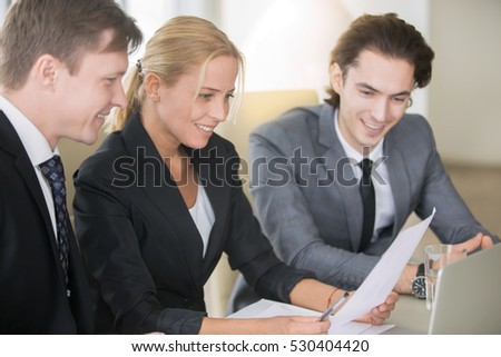 Group of three business partners discussing new project at meeting in office, looking pleased at paper document, commenting. Middle aged businesswoman showing company growth. Business success concept