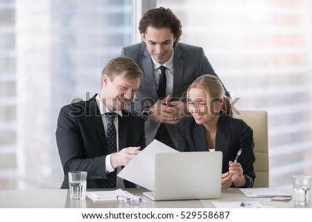 Group of three business partners discussing new project at meeting in office room, using laptop and document. Young confident businessman in formal wear suit explaining idea and showing work plan