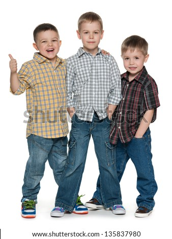 Group of three cheerful young boys are standing together; on the white background