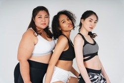 Group of three diverse women with asian and african in sport bra outfit over white background.