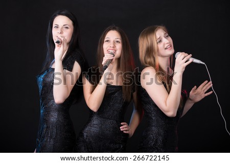 Group of three emotional beautiful young female singers with microphones singing, girls band concert