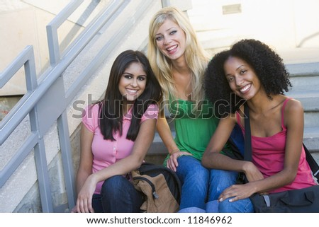 Group of three female university students sitting on steps