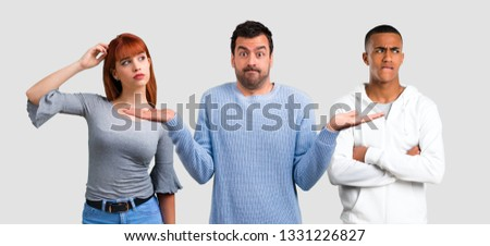 Group of three friends having doubts and with confuse face expression