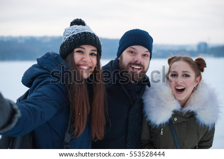 Group of three friends taking selfie photo in winter snow park