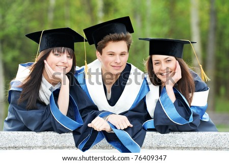 group of three graduation students in the park � cheerful and happy