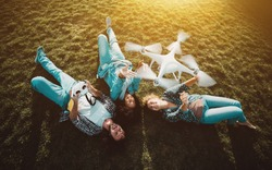 Group of three happy people: two girls of different races and one guy are laying on the meadow and posing to the drone, which is flying over them, operated by the bearded guy and capturing video