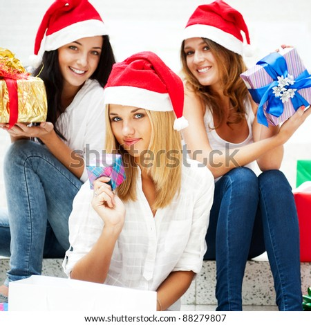 Group of three happy pretty girls are celebrating christmas and new year holidays wearing santa clause red hats and laughing with open arms