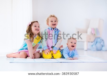 Group of three kids playing in a white bedroom. Children play at home. Preschooler girl, toddler boy and baby in nursery. Happy little brothers and sister bonding having fun together. Siblings love. Foto d'archivio ©