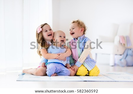 Group of three kids playing in a white bedroom. Children play at home. Preschooler girl, toddler boy and baby in nursery. Happy little brothers and sister bonding having fun together. Siblings love #582360592
